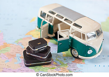 Vacation camper van with a stack of suitcases on a map
