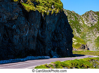 road under the cliff in high mountains. transportation...