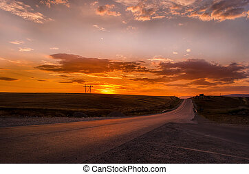 Road vanishing to the horizon under sun rays coming down trough the dramatic stormy clouds. Sunset at the mountain road. Azerbaijan, road to Shamakhi