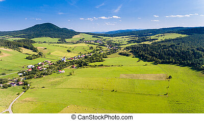 Road, village and mountain summer landscape from above - drone view