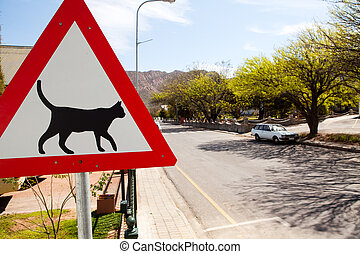 Road warning sign indicating cats are crossing - Triangular...