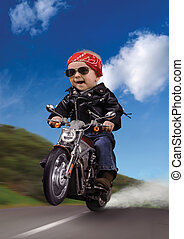 Road Warrior - Baby dressed as a biker, popping a wheelie on...