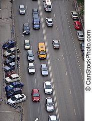 Road with car traffic. On the side of parked cars. Photo is made from a height.