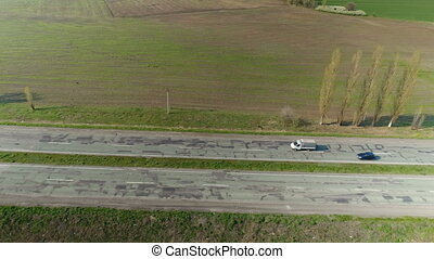 Flying over the old road with cars. Aerial survey