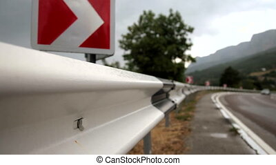 Road with Sign - Cars and trucks traverse a section of road...