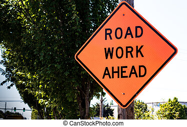Road work ahead sign on a post