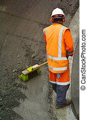 Road worker brooming remains of asphalt - Unrecognizable...