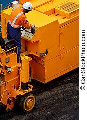 Road worker drives asphalt spreader during asphalt work repair