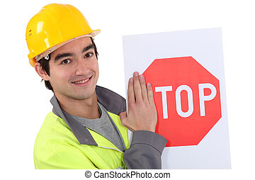 road worker hiding the letter s of a stop sign