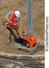 Road worker repairs asphalt  with hydraulic shifting reversible plates