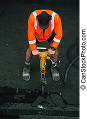 Road worker with a drill breaking up asphalt on the road....
