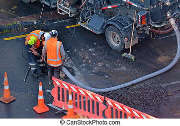 Road workers cleaning sewage in city street - Unrecognizable...