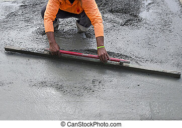 Road Working - Concrete - Builder is leveling cement during...