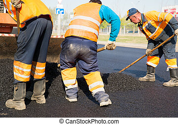 Road works - Construction workers during asphalting road...