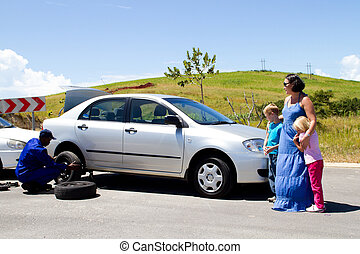 Roadside assistance - mechanic helping young mother with broken down car
