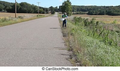 roadside cleanup - A man picks up trash along a rural road