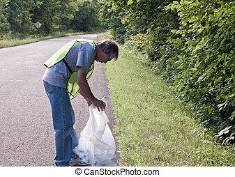 roadside cleanup - man picking up trash along a rural road