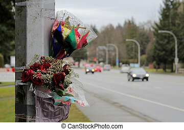 Roadside Memorial - Flowers are taped against a light ...