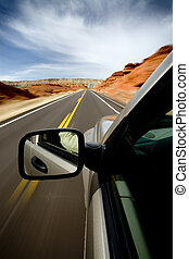 car driving through the Bighorn Canyon, Wyoming, with motion blur. SUV, focus on mirror.