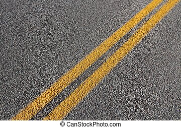 Asphalt concrete roadway pavement surface. Grey background with yellow line.