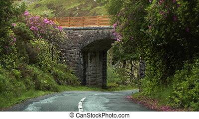 Roadway passing under a stone bridge