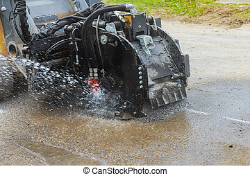Roadworks scraping road machine removes old asphalt during construction