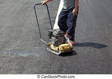 Roadworks - Worker with compactor at a road construction ...
