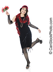 Full-length image of a beautiful teen girl happily dancing the Charelston while holding a small bouquet of red flowers. On a white background.