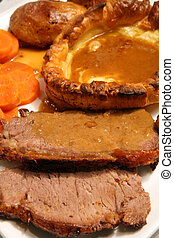 Extreme close-up on a traditional English Sunday lunch of roast beef and yorkshire pudding, with carrots, roast potato and gravy