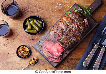 Roast beef on cutting board. Wooden background. Top view.