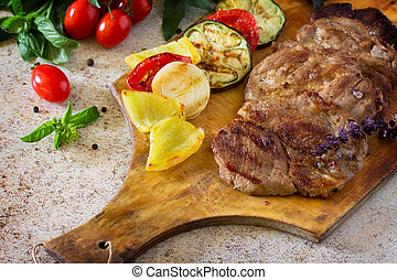 Roast beef or pork with sauce and grilled autumn vegetables: peppers, onions and eggplant on a concrete brown background. Food Concept Thanksgiving.