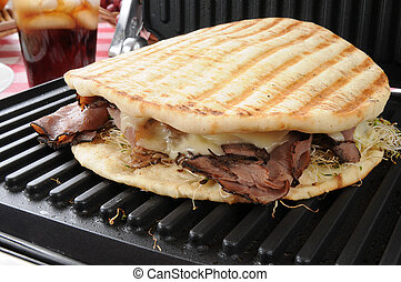 Roast beef sandwich on a panini press - a roast beef panini...
