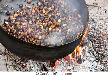 roast chestnuts cooked on wood fire, roasting pan with holes