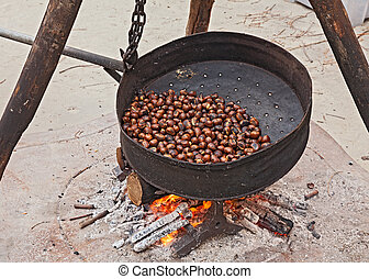roast chestnuts cooked on wood fire, in roasting pan with...