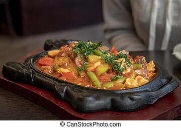 Roast meat with vegetables and gravy in a cast-iron pan.