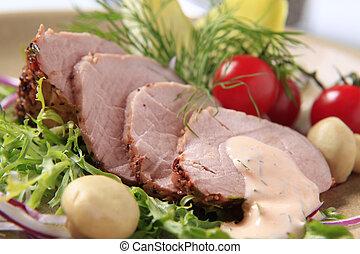 Roast pork tenderloin served with vegetables - detail