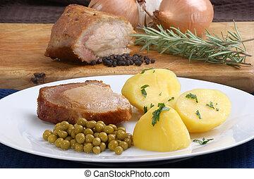 Roast pork with roast potatoes and peas