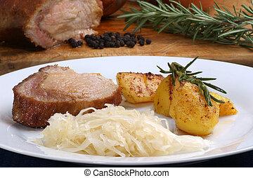 Roast pork with roast potatoes and sauerkraut