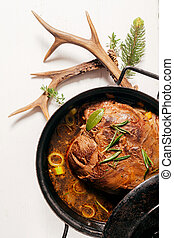 Roast Venison Seaseoned with Fresh Herbs in Pot - High Angle...