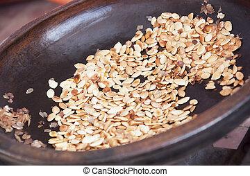 Roasted argan kernels in a frying pan. - Argan kernels from...