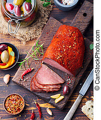 Roasted beef, pastrami on wooden cutting board
