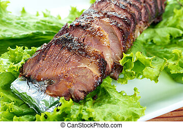 Sliced roasted beef with lettuce on plate