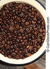 Roasted brown coffee beans in a bowl