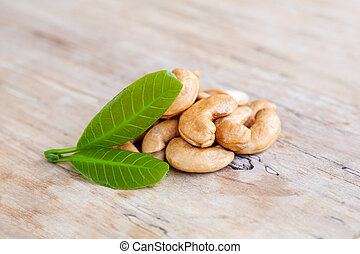 Roasted cashew nuts with fresh leaves.