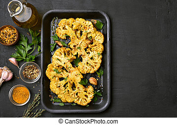 Roasted cauliflower steaks with herbs and spices on baking...