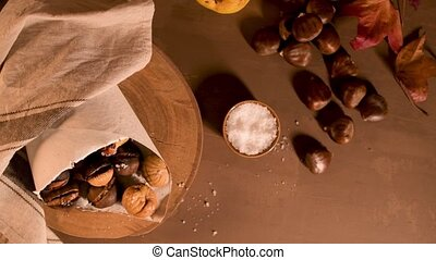 Roasted chestnuts in a paper cone, on a rustic kitchen...