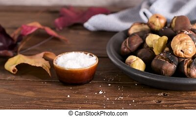 Roasted chestnuts in cast iron pan over rustic wooden board...