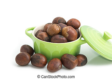 roasted chestnuts in green bowl on white background