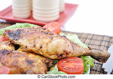 Roasted chicken drumsticks and vegetables and saltshaker