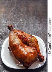 Roasted chicken legs cooked on a barbecue on a white plate on a black background. Top view from above. Copy space